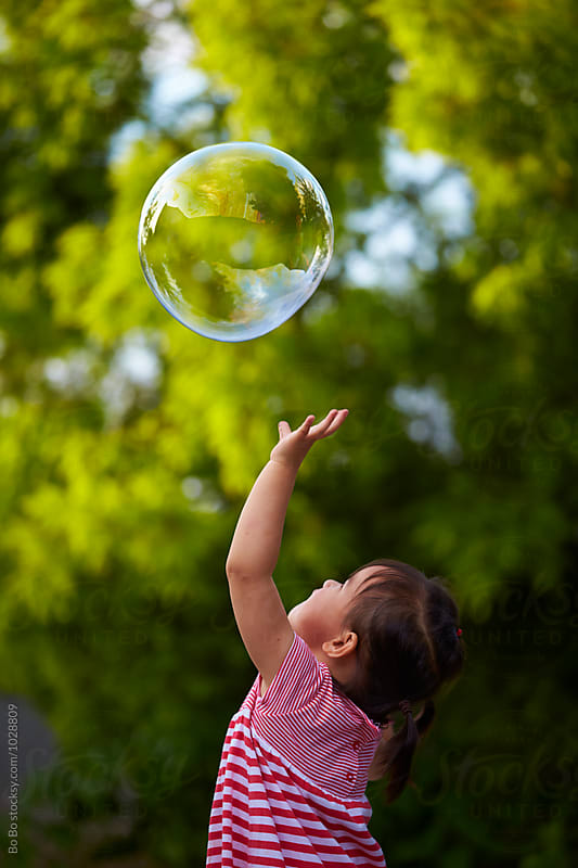 little asian girl trying to catch soap bubble by Bo Bo for Stocksy United