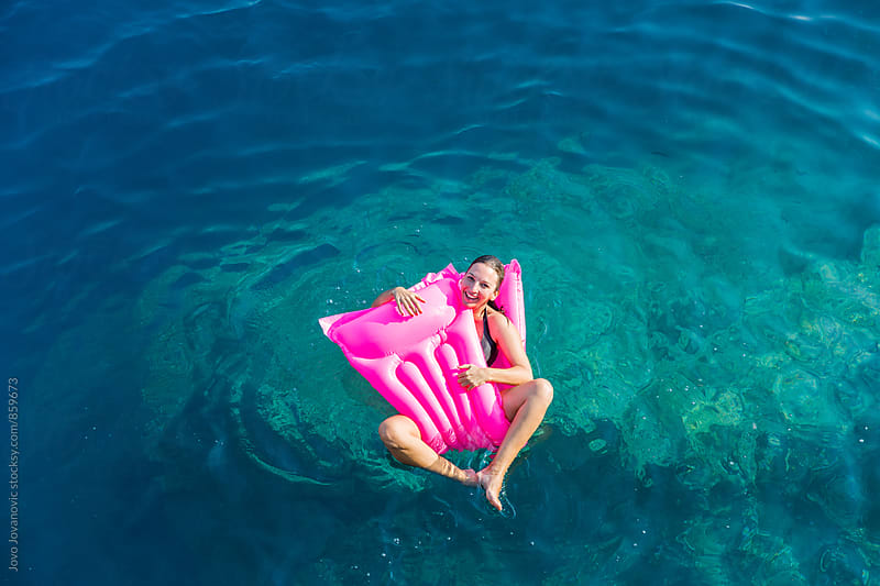 Beautiful young woman smiling on a bright pink float in the ocean  by Jovo Jovanovic for Stocksy United