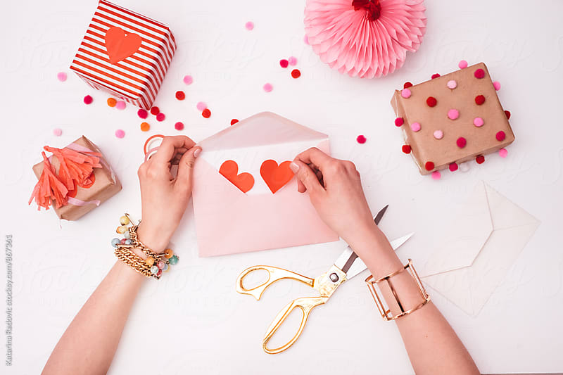 Woman Putting Red Hearts in a Pink Envelope  by Katarina Radovic for Stocksy United