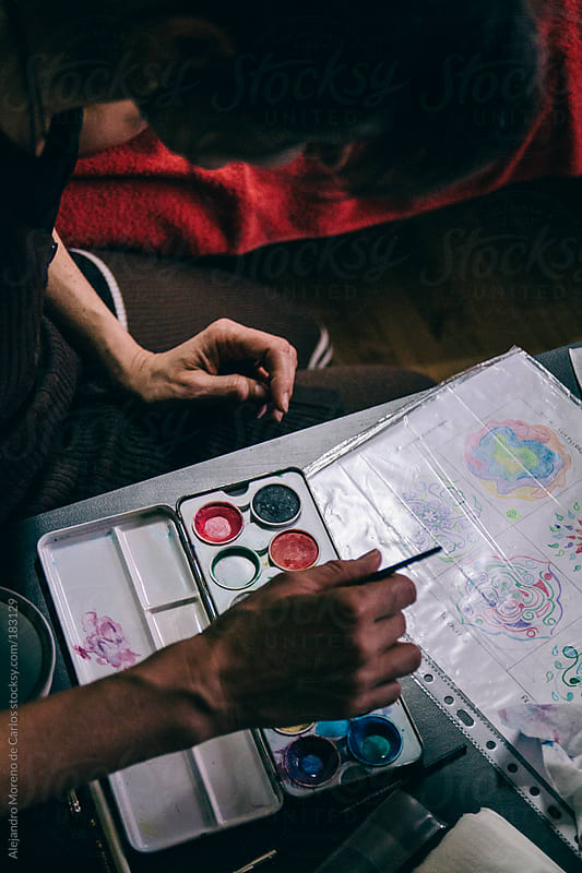 Overhead of watercolors palette and head of artist painting a mandala by Alejandro Moreno de Carlos for Stocksy United