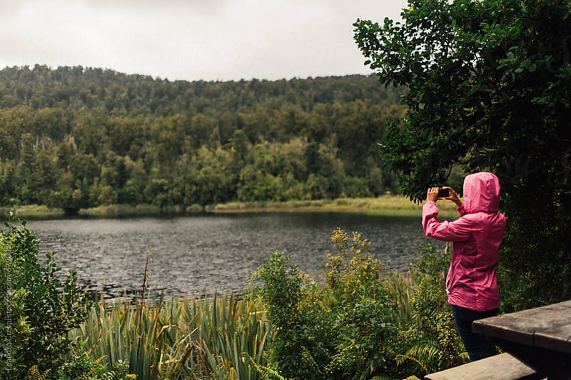 Woman taking a picture of a hidden lake in a forest with a smartphone  by Leandro Crespi for Stocksy United