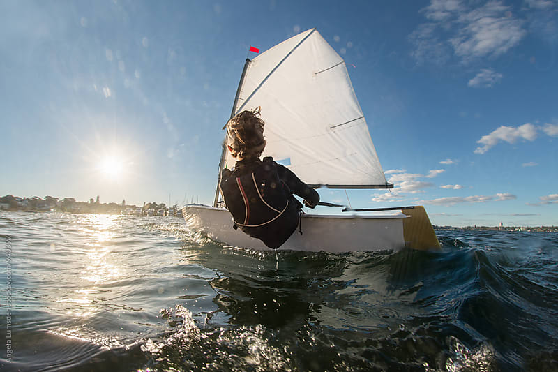 Child sailing an optimist class dinghy viewed from behind by Angela Lumsden for Stocksy United