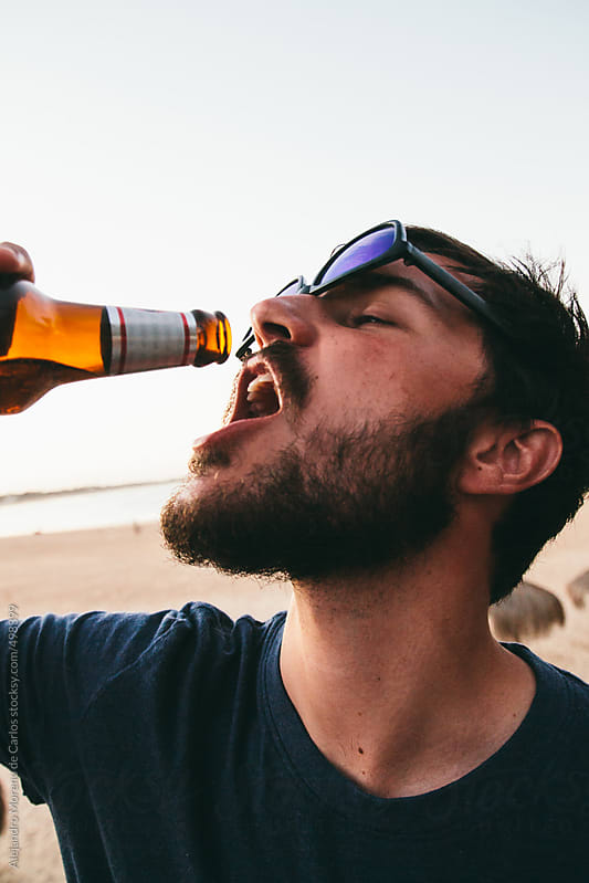 Young man drinking from a bottle of beer on the beach by Alejandro Moreno de Carlos for Stocksy United