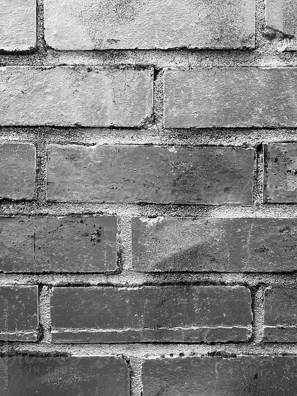 Silver paint covering graffiti tags on brick wall, close up by Paul Edmondson for Stocksy United