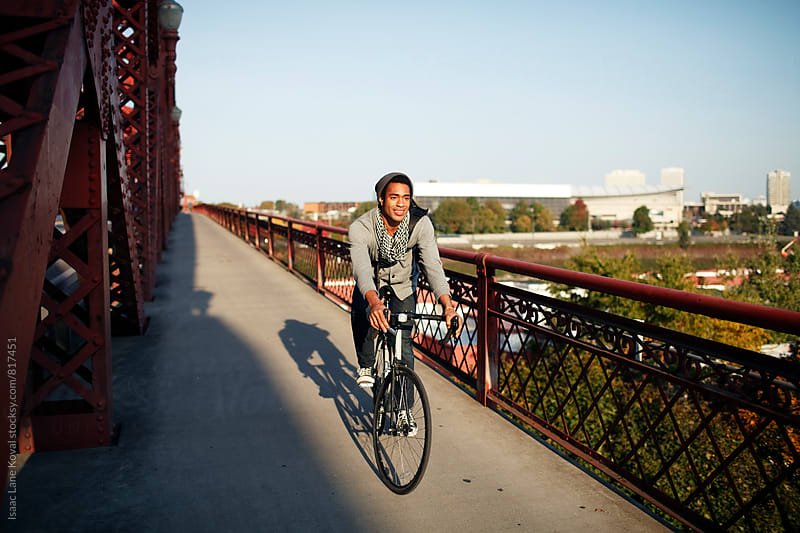 Man riding bike across bridge by Isaac Lane Koval for Stocksy United