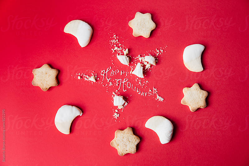 Star and moon shaped cookies on red background by Beatrix Boros for Stocksy United