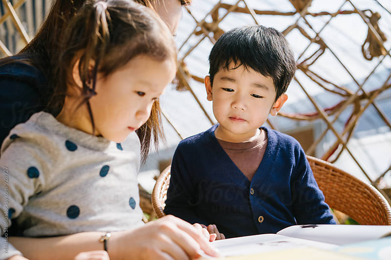 Young chinese mother reading with her children by MaaHoo Studio for Stocksy United