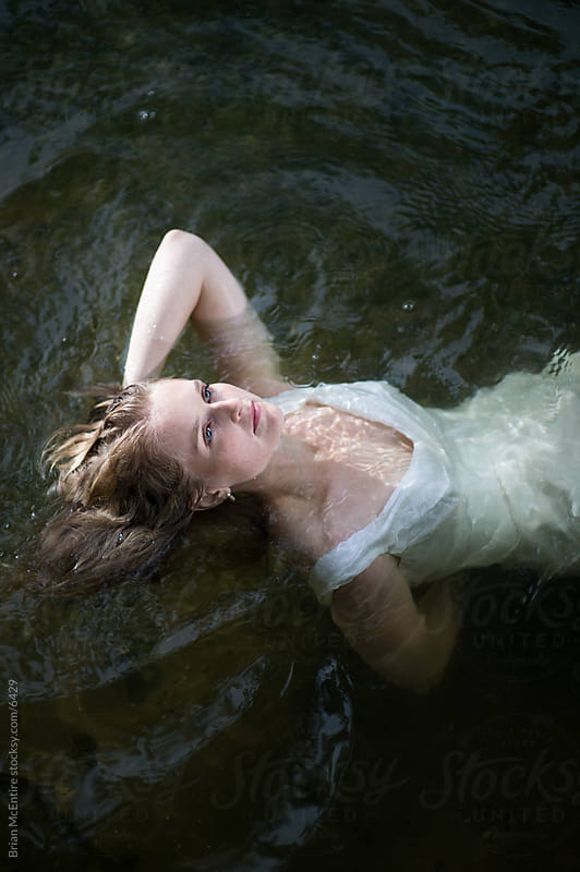 Woman in white wedding dress floating in natural water by Brian McEntire for Stocksy United