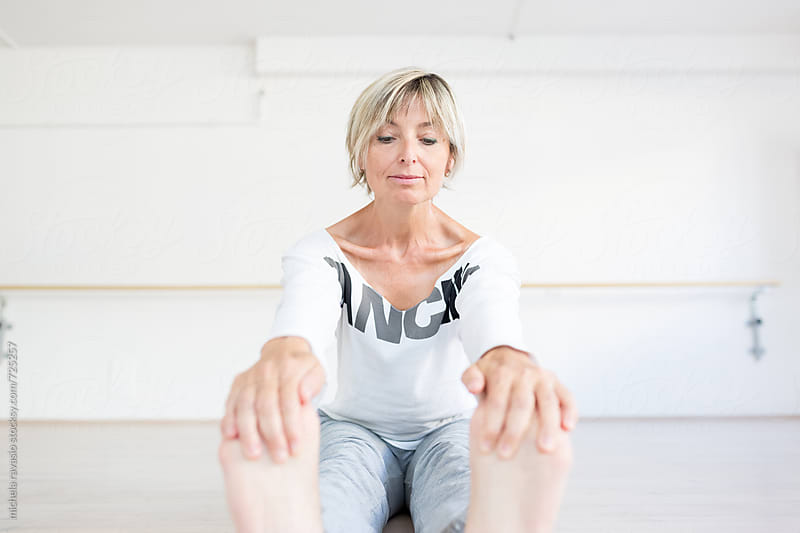 Mature woman doing stretching by michela ravasio for Stocksy United