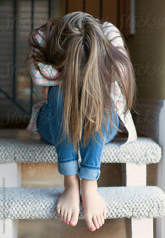 Teenage girl with long hair - head down hiding her face by Carolyn Lagattuta for Stocksy United