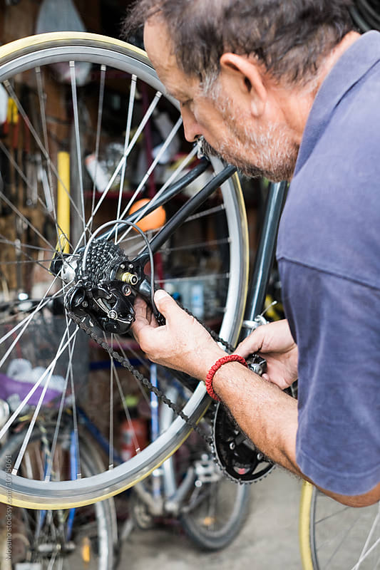 Man Repairs a Bike  by Mosuno for Stocksy United