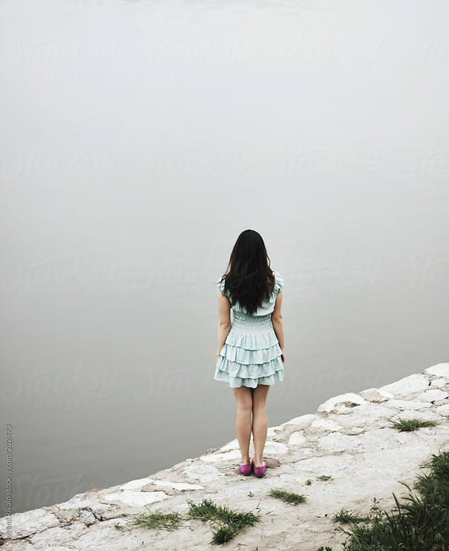Back view of a woman standing on the edge of the river dock by Jovana Rikalo for Stocksy United