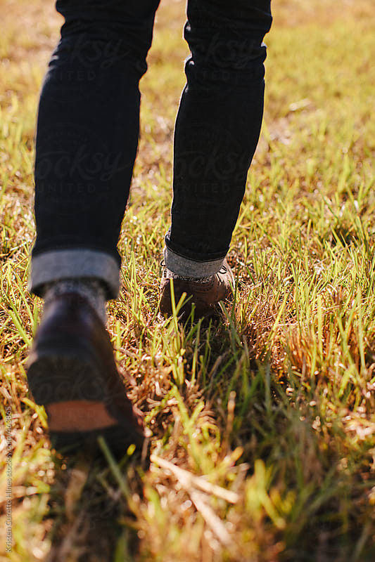Close up of mens dress shoes walking through the grass by Kristen Curette Hines for Stocksy United