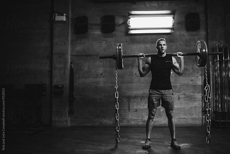 Strong caucasian man lifting weights with chains in gritty workout gym by Rob and Julia Campbell for Stocksy United