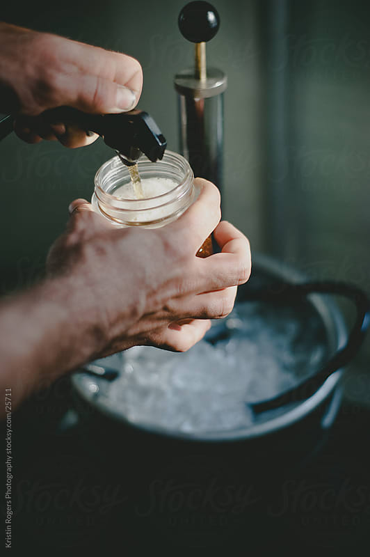 close up of hands getting a beer from a keg by Kristin Rogers Photography for Stocksy United