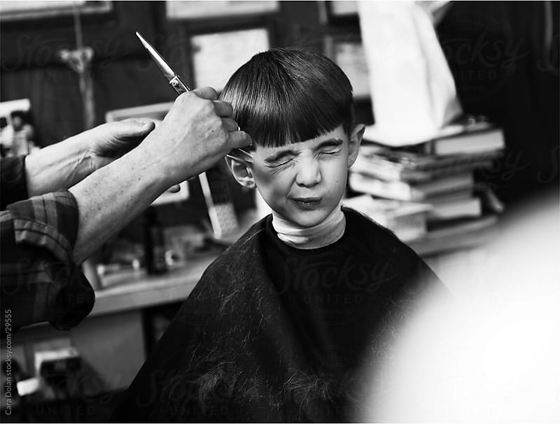 Boy grimaces as he gets his hair cut by Cara Slifka for Stocksy United