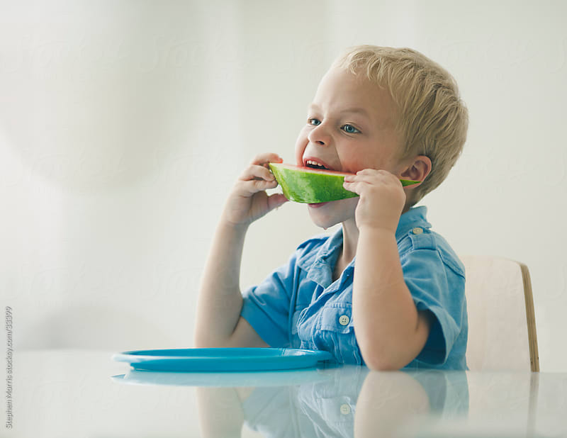 Boy Eating Watermelon in Modern Dining Room by Stephen Morris for Stocksy United