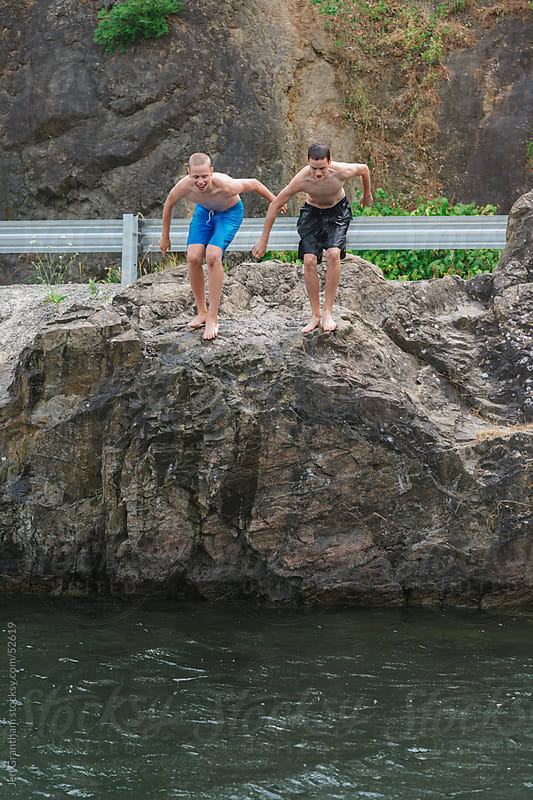 Teen boys jumping into lake by Jen Grantham for Stocksy United