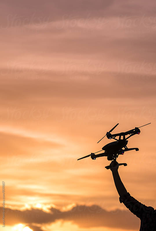 Man using a drone in the cloudy sunset by Luca Pierro for Stocksy United