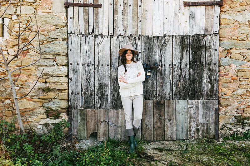 Brunette woman farmer standing in front of a wooden wall. by BONNINSTUDIO for Stocksy United