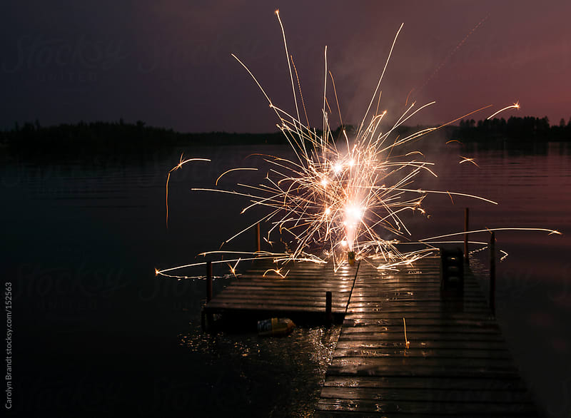 fireworks off of a dock by Carolyn Brandt for Stocksy United
