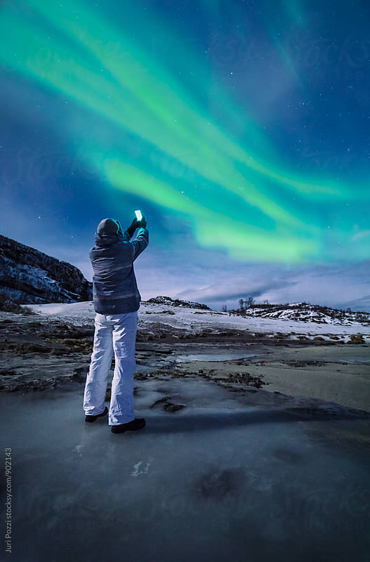 man taking a snapshot of northern lights by Juri Pozzi for Stocksy United