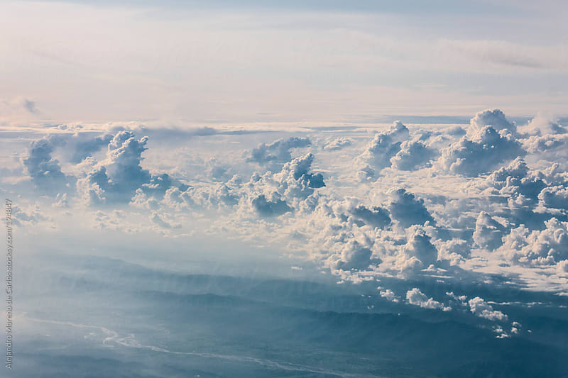 Clouds from above. Aerial view of sky and a river by Alejandro Moreno de Carlos for Stocksy United