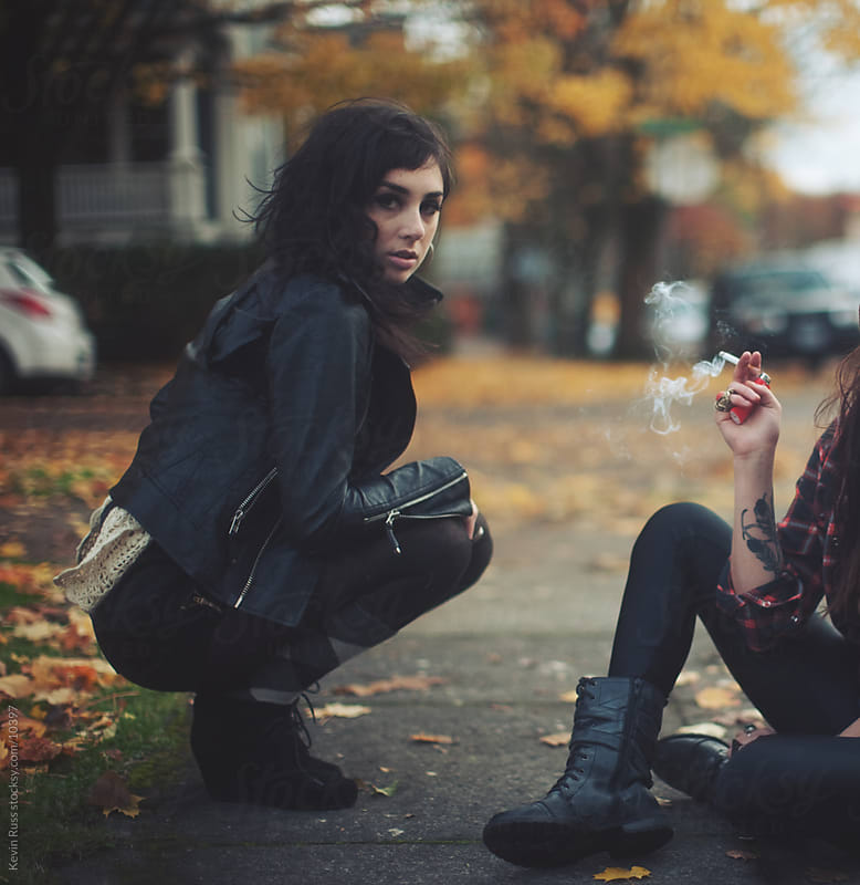 Outdoor Sidewalk Crouch and Smoking Women by Kevin Russ for Stocksy United