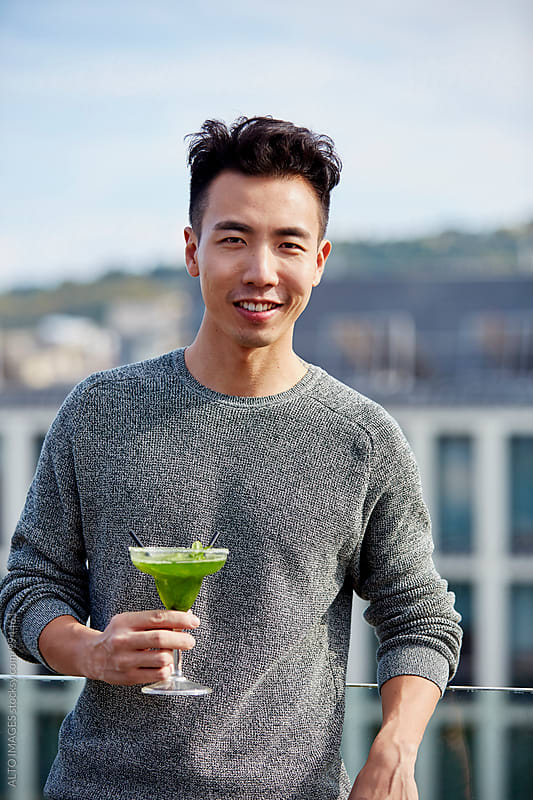 Man Holding Glass Of Cocktail On Hotel Terrace by ALTO IMAGES for Stocksy United