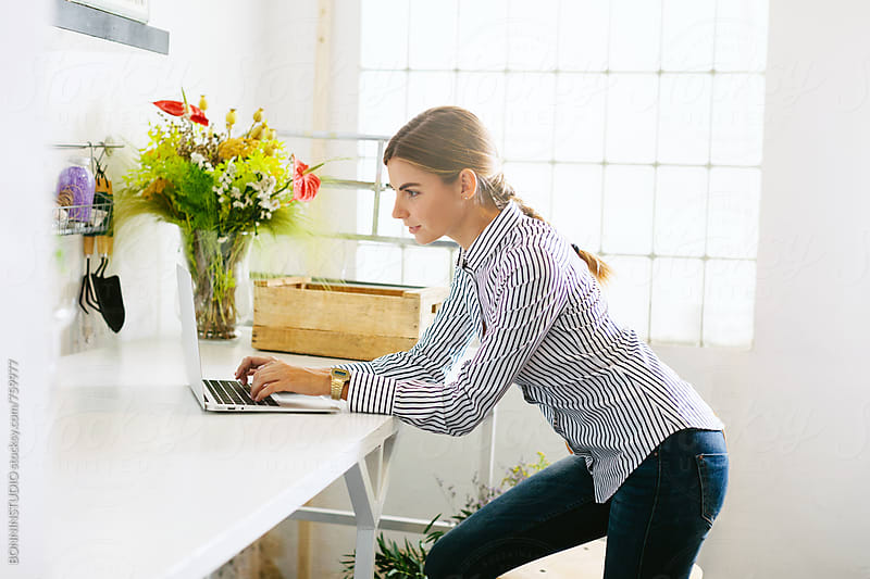Businesswoman typing on her laptop standing at office. by BONNINSTUDIO for Stocksy United