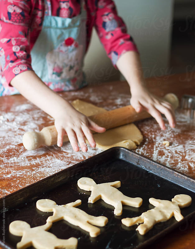 A little girl baking biscuits by Helen Rushbrook for Stocksy United