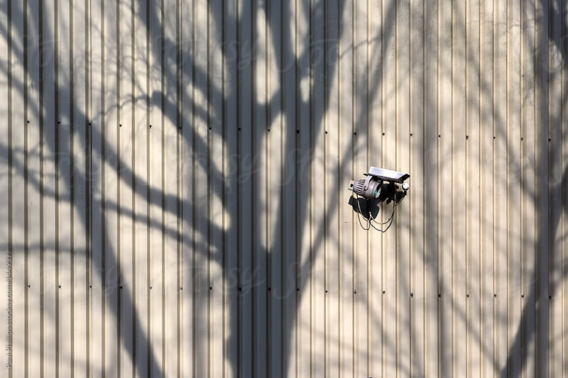 Wall of industrial building with security camera and shadow of tree by Paul Phillips for Stocksy United