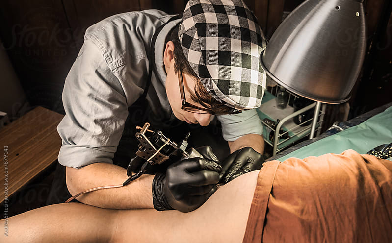 Young tattoo artist in vintage outfit inking female legs/look from above by Audrey Shtecinjo for Stocksy United
