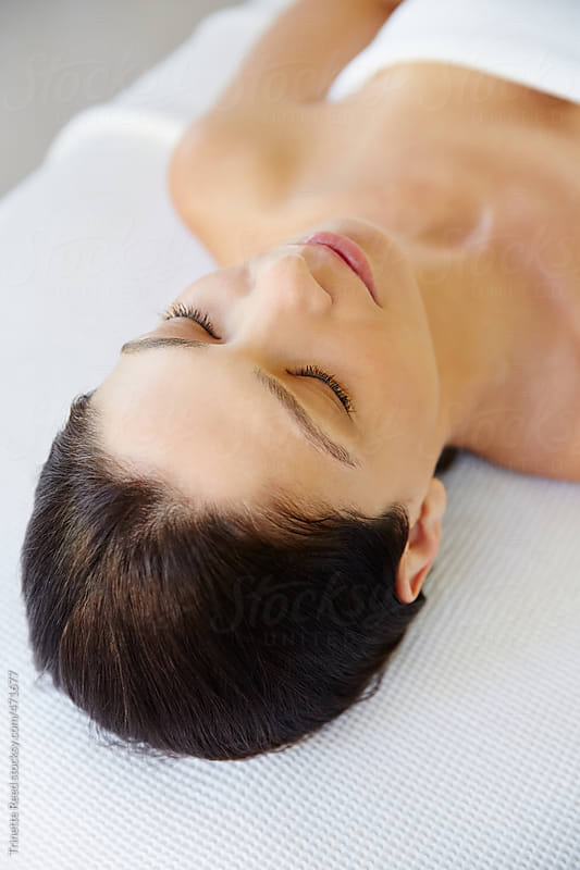 Beautiful woman relaxing on massage table for facial spa treatment  by Trinette Reed for Stocksy United