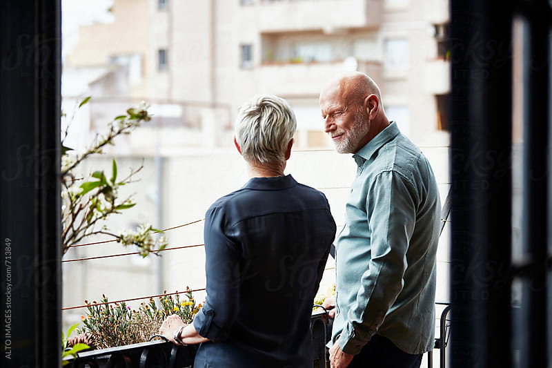 Senior Couple Conversing On Balcony by ALTO IMAGES for Stocksy United