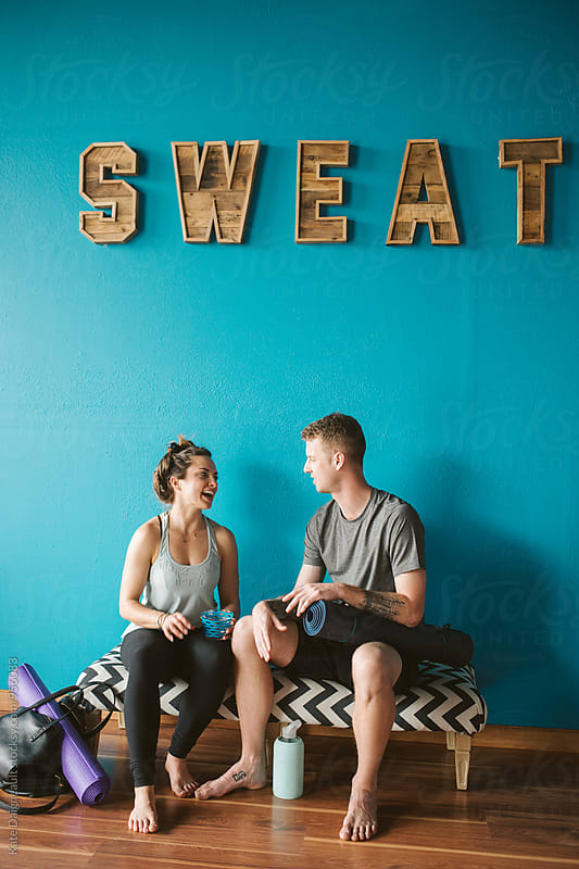 Two young adults hanging out after a yoga class by Kate Daigneault for Stocksy United