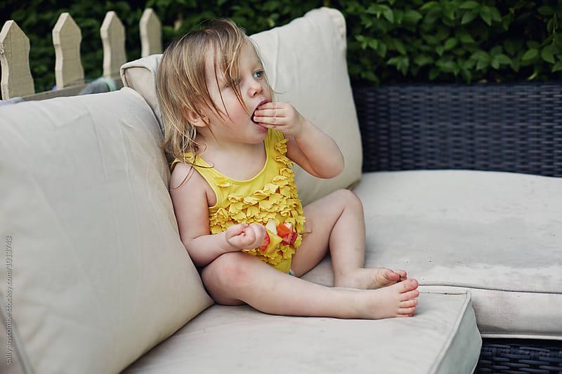 Little toddler girl eating fruit by sally anscombe for Stocksy United