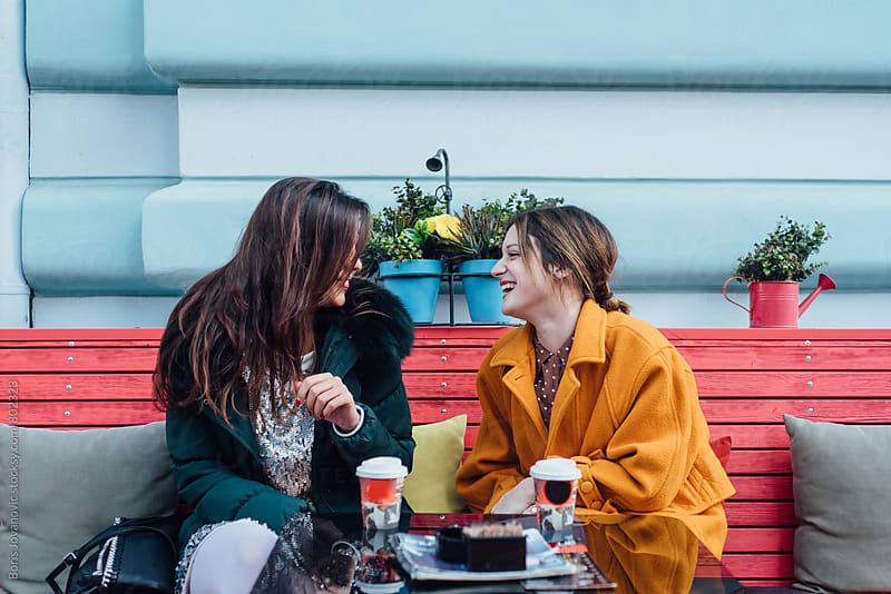 Girlfriends having a fun talk in the cafe by Boris Jovanovic for Stocksy United
