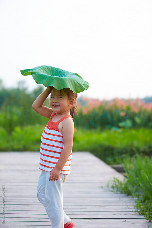 lovely little asian girl playing with lotus leaf outdoor by Bo Bo for Stocksy United
