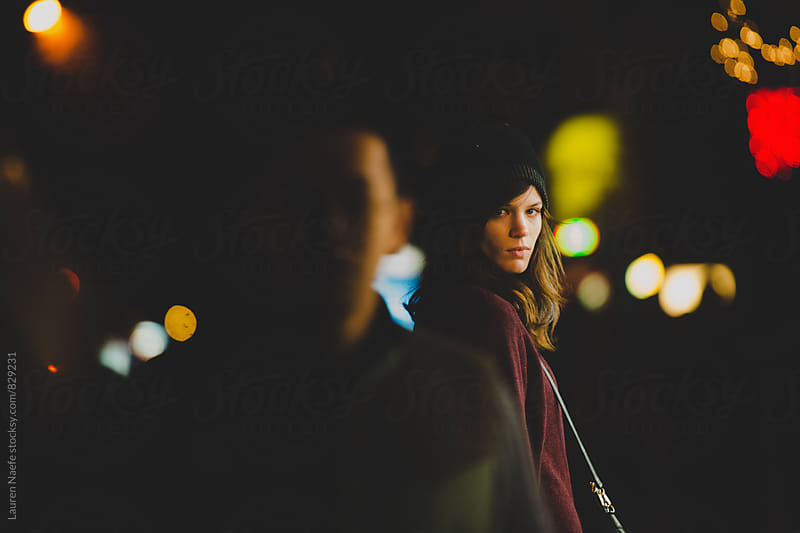 Young woman in the city at night by Lauren Naefe for Stocksy United
