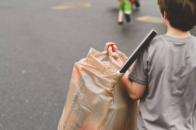 boy carrying shopping bag by Jess Lewis for Stocksy United