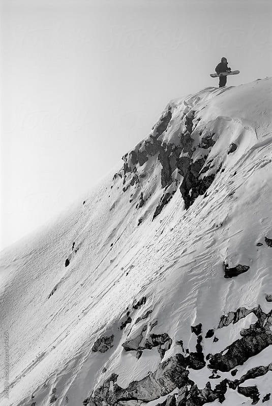 snowboarder checking a cliff jump on snow mountains by Jan Bijl for Stocksy United