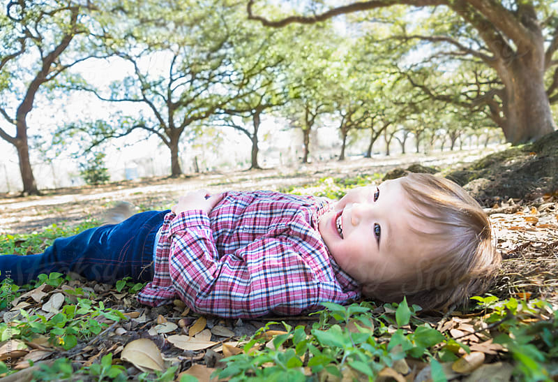 Little boy, lying down on the ground at a park by yuko hirao for Stocksy United