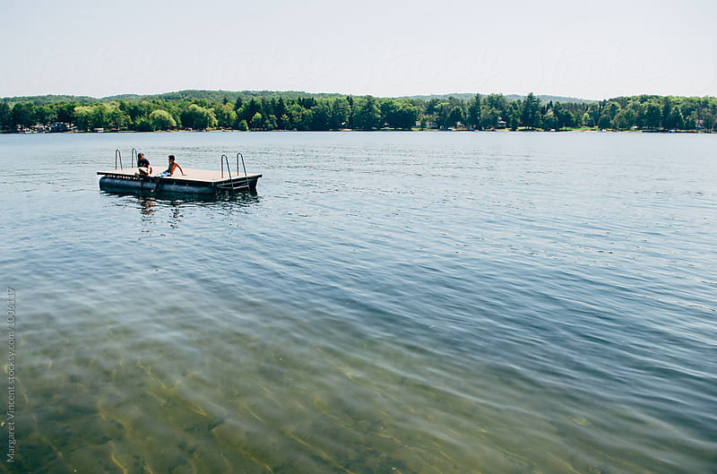 two teenagers talking on a raft in a lake by Margaret Vincent for Stocksy United