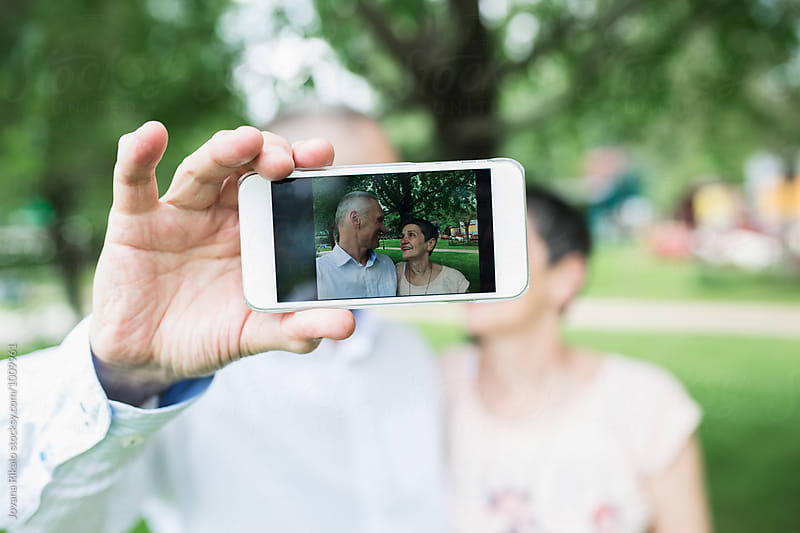 Elderly couple taking selfie in nature by Jovana Rikalo for Stocksy United