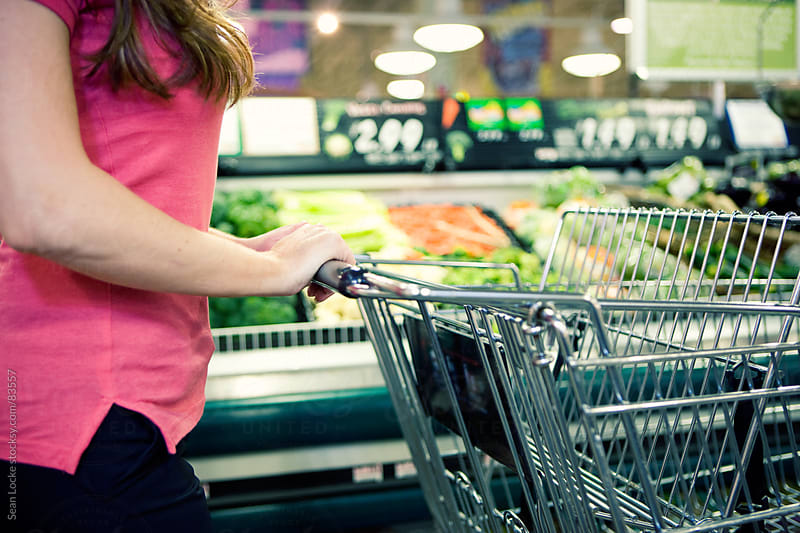 Grocery: Woman Pushes Shopping Cart by Sean Locke for Stocksy United