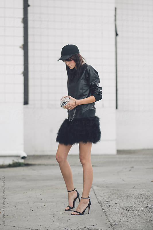 A woman dressed in all black checking the contents of her purse by Ania Boniecka for Stocksy United