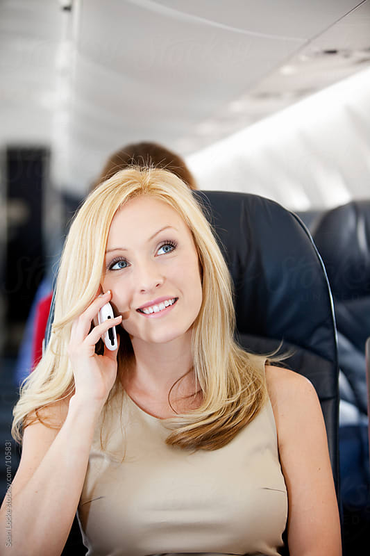 Airplane: Woman On Cell Phone In Flight by Sean Locke for Stocksy United