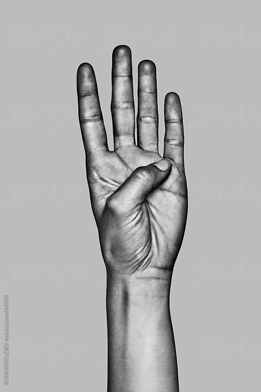 Hand making the number four sign. Black and white photo. by BONNINSTUDIO for Stocksy United