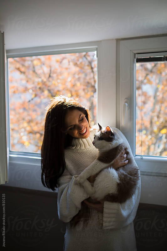 Young woman holding her cat by Jovana Rikalo for Stocksy United